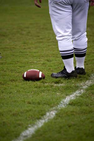 De benen van voet bal officiële zoals hij naast een voet bal ligt geplaatst ter plaatse