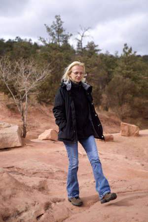 A mature woman on a cool day walking or hiking through a rocky western setting photo