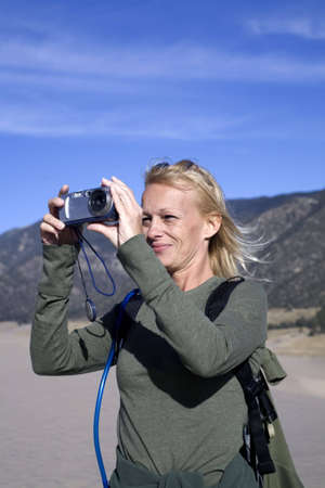 A woman hiker standing on a sand dune taking a photograph with a small camera photo