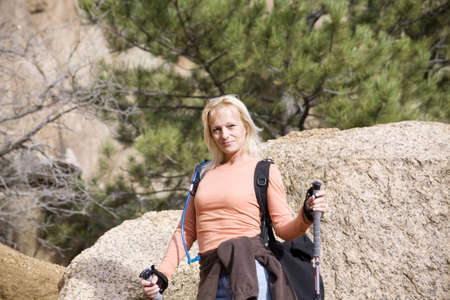 Sexy woman hiking in the mountains of Colorado, holding hiking poles photo