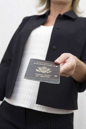 internationally: Woman holds out diplomatic passport for inspection in travling internationally.  Stock Photo