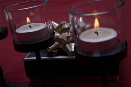 atmosphere: Small gift box on a red background behind a candle set creating a romantic atmosphere.