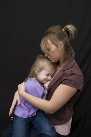 A young mother hugging her sad daughter. Shot from profile capturing the unhappy look on the little girls face.