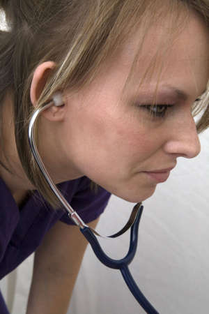A female medical professional with stethoscope in her ears listening intently.  Imagens
