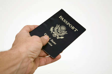 Handing over an American passport. Shot from the perspective of the passport owner handing out into a white background. Stock Photo