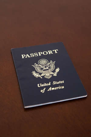 American passport laying on an angle on a wooden desk.  photo