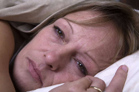 Sad looking adult woman laying covered in bed. Closeup on face with blank depressed look. Stock Photo