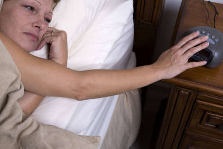 Shot from above of woman reaching for alarm clock. Sleepy, depressed look as female pushes snooze button on alarm. photo