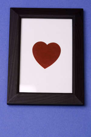 though: A heart symbol on a white background in a wooden black frame on a blue background.  Shot as though looking up at it on a wall. Heart is easily isolated and removed so that any text or image can be framed.