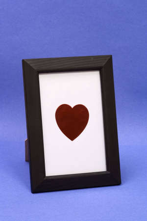 Heart symbol in a desk type picture frame shot on an angle. Isolated on blue background with white inside frame to isolate heart.