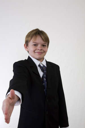 hair tie: boy in business type suit holding his hand out to extend a handshake offer. Making childs play of business, kid dressed up offering greeting.