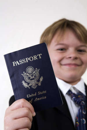 A young boy holding up a passport for inspection. Dressed in a business style suit to create a business theme, a child holds out his passport with focus on the id.