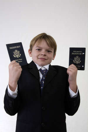 A boy holding up two passports with a questioning look on his face.