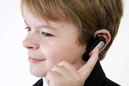 Young man listening intently on a wireless headset with a smile. Childs play of customer service on the phone. photo