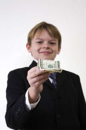 A young man holding out an American 5 dollar bill.  Focus on the money.  photo