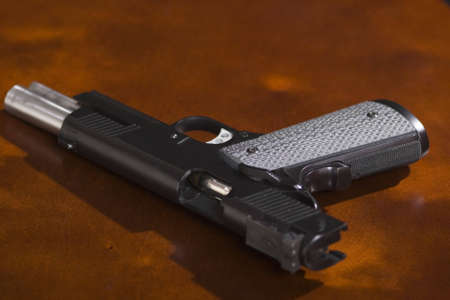 A 1911 model 45 caliber pistol on a bright cherry desk with slide open. Shot in low depth of field with stark lighting to create an ominous atmosphere. photo