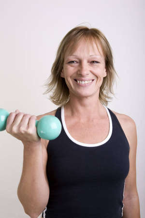 40s adult: A 40s adult woman doing a bicep curl with a dumbbell to get in shape. Loosing weight after the holdiay feasting.