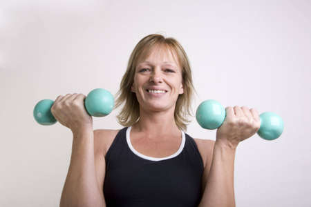 Woman exercising off holiday weight gain with dumbbells. Double bicep curl fronal shot. Stock Photo