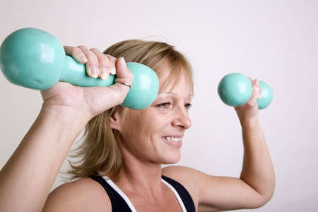 40s adult: 40s adult woman staying in shape with exercise. Side shot of lady doing shoulder presses with weights.