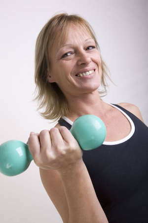 Woman doing bicep curls with dumbbells isolated on solid background.