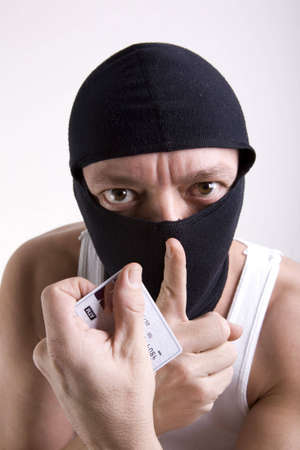 A thief with a mask on his face and a credit atm card in his hand signaling for silence.