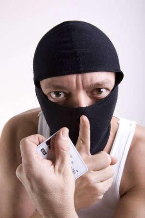 Un ladrón con una máscara en su rostro y una tarjeta de crédito en cajeros automáticos en la mano para indicar silencio. Foto de archivo - 4000425