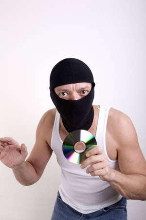datos personales: Ladr�n enmascarado con un CD en la mano. Robo de empresa o datos personales en el disco. Foto de archivo