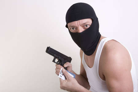 A masked armed thief with a handful of stolen credit cards. photo