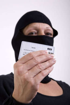 stole: A female masked thief holds up a bank credit card, as if to show off that she stole your credit.