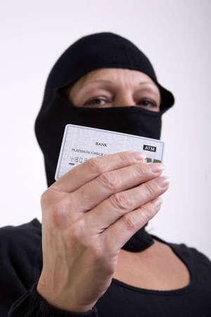 stola: Eine weibliche maskierte Dieb h�lt eine Bank Kreditkarte, als ob zu zeigen, dass sie gestohlen Ihrer Kreditkarte.