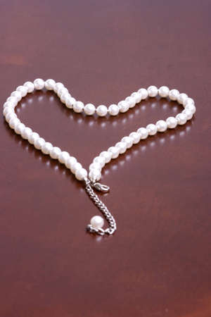 A romantic gift reminder idea of a string of pearls in the shape of a heart. Win your special lady over with pearls on Valentines day. photo