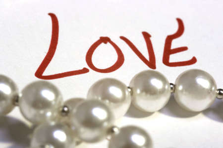 The word love in focus behind a string of pearls. Stock Photo - 4012490