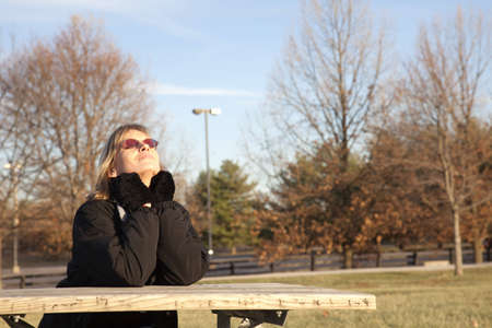 Offset with copy space to the right, a woman sitting at a park picnic table enjoying the warmth of the sun. Stock Photo