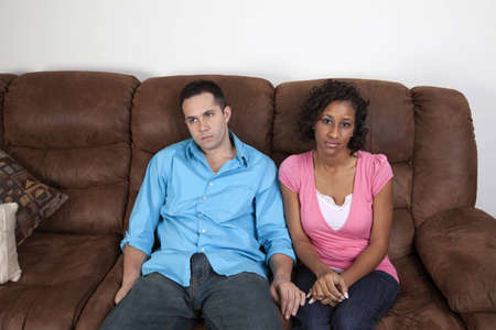 A couple sitting on the couch side by side looking very bored