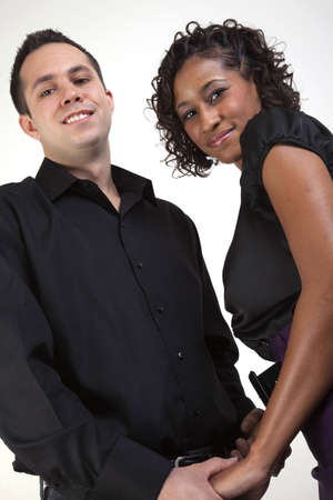 Interracial couple holding hands and smiling while facing each other Stock Photo - 4136716