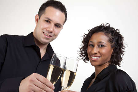An interracial couple toasting with champagne