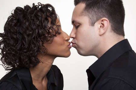 Couple sharing a soft kiss, shot in profile. Stock Photo