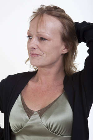 A woman with a smirky smile holding her hair back Stock Photo