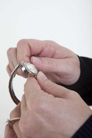 daylight savings time: Female hands adjusting the time on a watch. Daylight Savings Time theme.