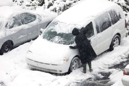 A person scraping snow and ice during the ice storm in Louisville, Kentucky Stock Photo