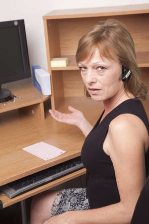 earpiece: Business woman showing surprise at being laid off with a pink slip on her desk