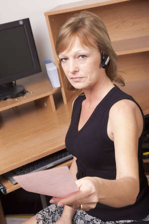 earpiece: A female business woman giving a pink slip while seated at her desk.  Stock Photo
