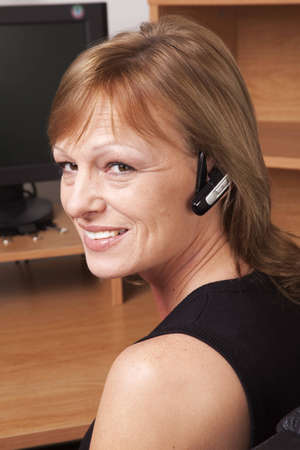 earpiece: A business woman with a phone earpiece smiling at her desk.