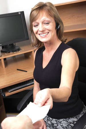 earpiece: A businesswoman smiling at getting a blank check while seated at desk Stock Photo