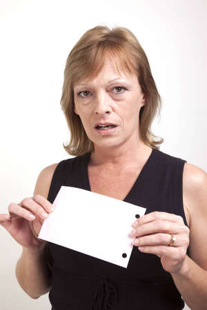 A mature business woman showing surprise while holding up a blank pink slip of paper