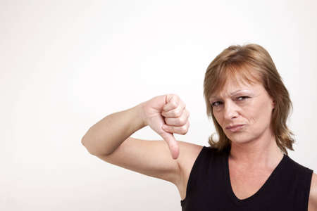 Mature adult female frowning while giving a thumb down signal Stock Photo