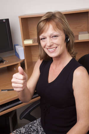 A business woman giving a thumbs up sign at her office desk