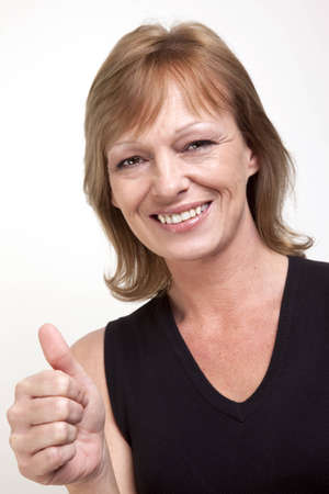 Mature woman smiling and giving a thumbs up signal Stock Photo