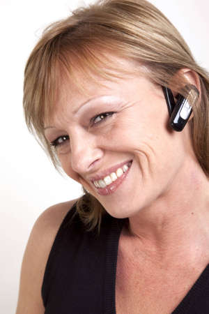 earpiece: A beautiful mature woman with a wireless earpiece and head tilted to side