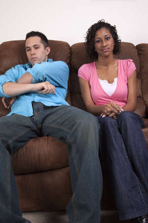 A couple sitting on a couch with unhappy looks. Regret over an argument paired with mad over something said 版權商用圖片